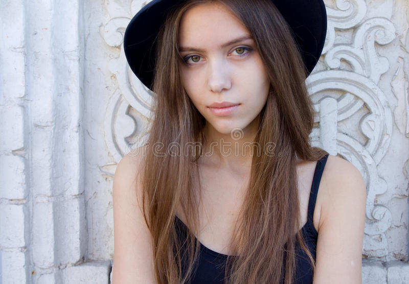 Portrait of a beautiful young adult girl in black hat outdoor stock images