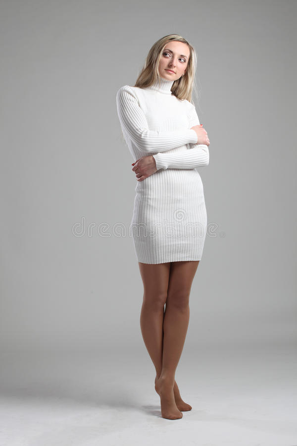 Portrait of a beautiful young adult slim and attractive sensuality pretty blonde woman in white elegance fashionable sweater stock image