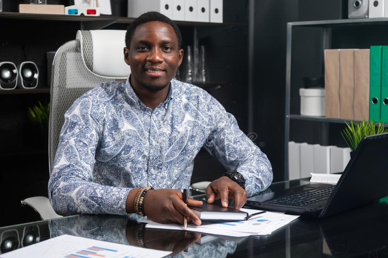 Portrait of Beautiful young African American businessman working with documents and laptop in office. Successful young African man sits at his Desk in office and stock images