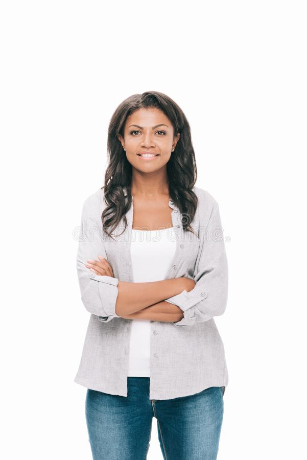 portrait of beautiful young african american woman with crossed arms smiling at camera stock photos