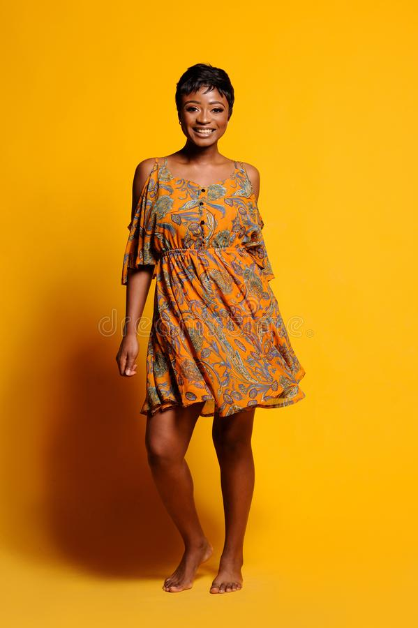 Portrait of a beautiful young African woman over yellow background. Studio picture stock photos
