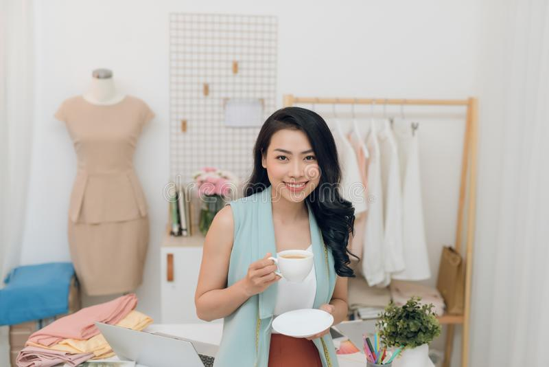 Portrait of beautiful young Asian fashion designer businesswoman at her studio while drinking coffee royalty free stock photos