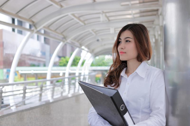 Portrait of beautiful young Asian secretary woman holding ring binder at sidewalk of office with copy space. royalty free stock images