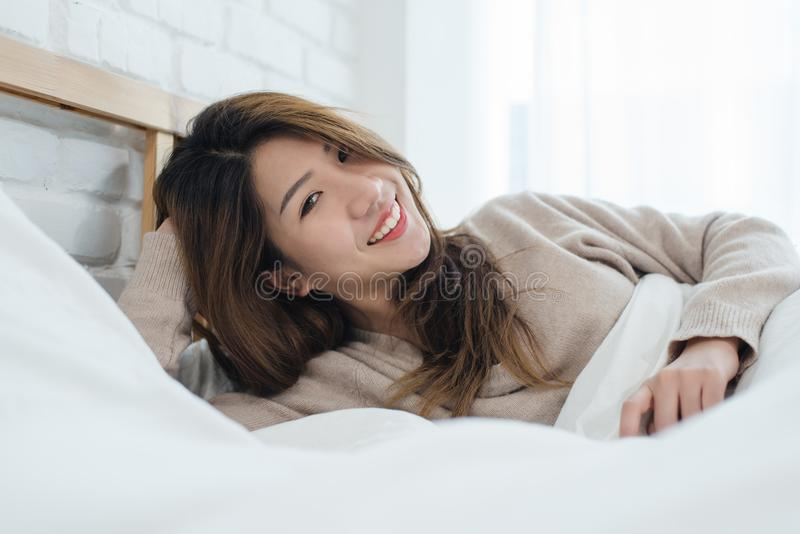 Portrait beautiful young Asian woman on bed at home in the morning. royalty free stock photography