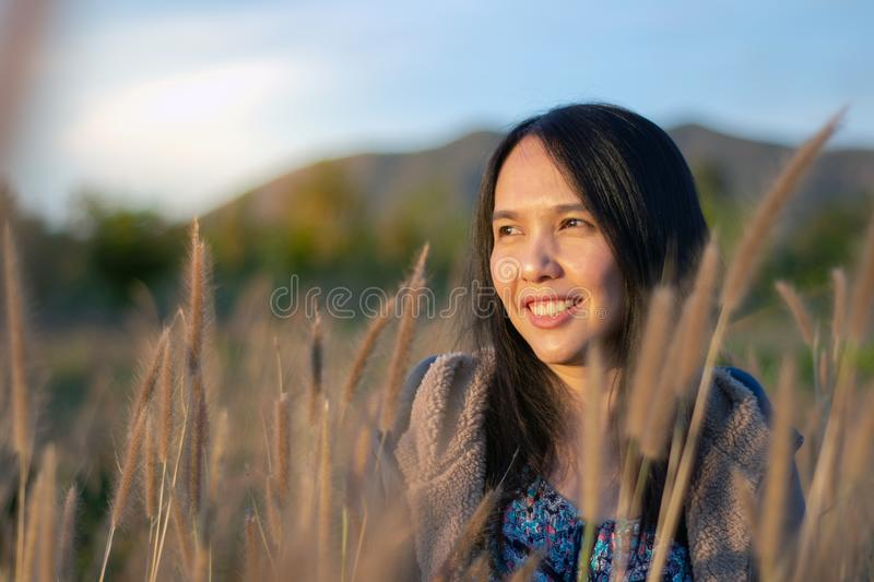 Portrait of beautiful young Asian woman enjoying nature on grass meadow at sunrise stock images