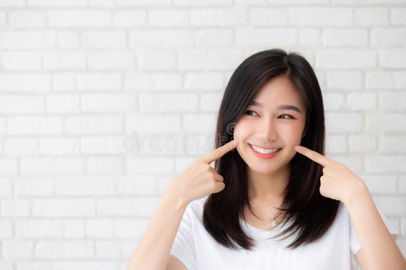 Portrait of beautiful young asian woman happiness standing finger touch cheek on gray cement texture grunge wall brick background. Businesswoman is a smiling royalty free stock photos