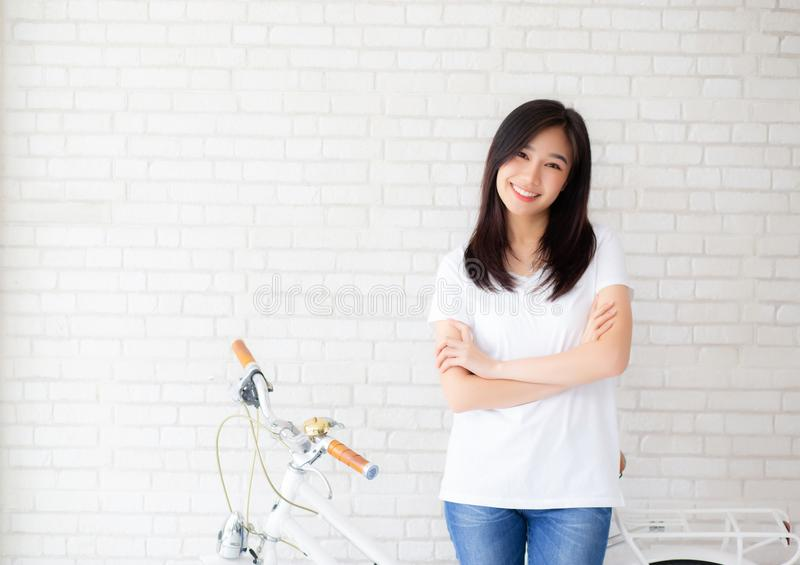 Portrait of beautiful young asian woman happiness standing on gray cement texture grunge wall brick background. stock photo