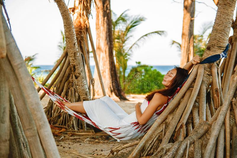 Portrait beautiful young asian woman happy smile leisure on hammock swing around the beach sea and ocean with blue sky white cloud royalty free stock image