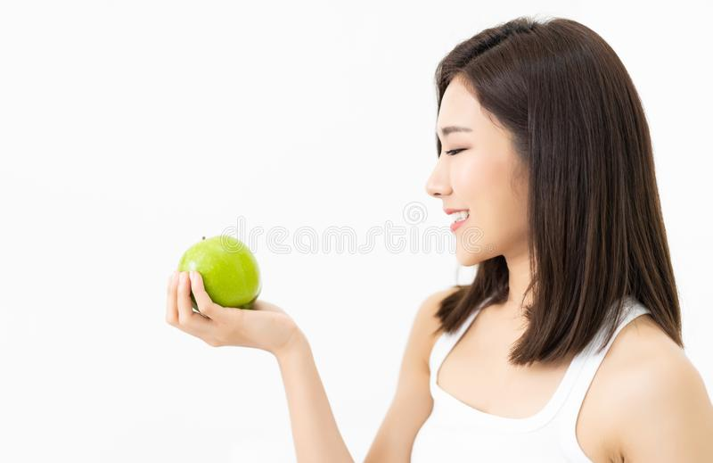Portrait of a beautiful young Asian woman looks at hands holding green apple isolated on white background.Healthy food and people. Concept royalty free stock photography