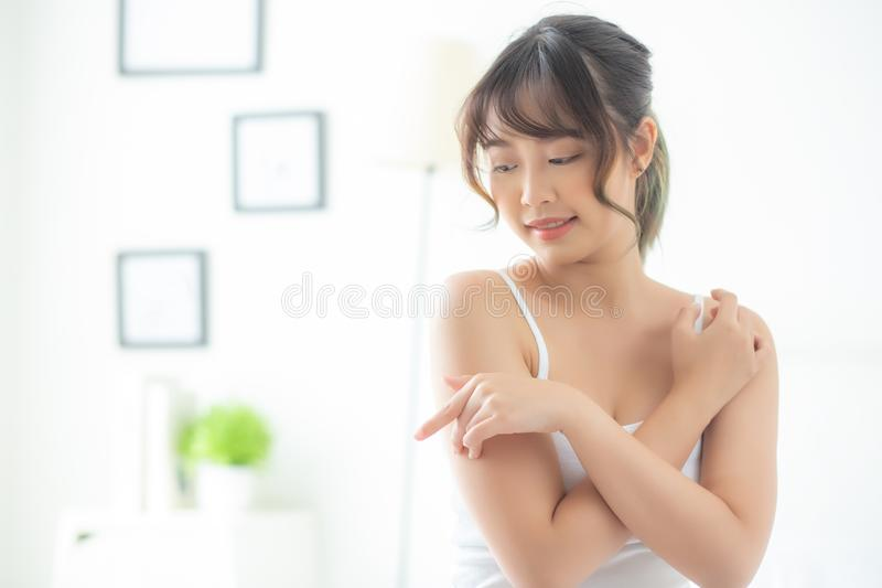 Portrait of beautiful young asian woman makeup of cosmetic, girl hand touch shoulder and smile attractive. Face of beauty perfect with wellness in the bedroom stock image