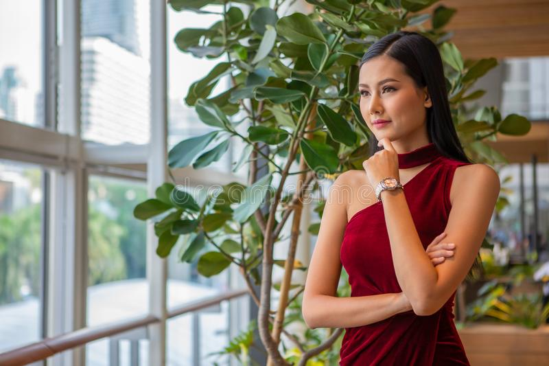 portrait of Beautiful young asian woman in red dress standing and looking out the window . elegant lady model positive thinking stock image