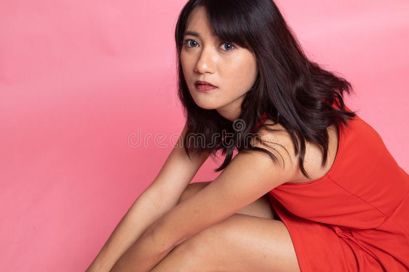 Portrait of  beautiful young asian woman sit on floor. On pink background royalty free stock images