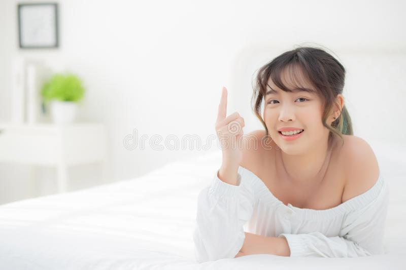 Portrait beautiful young asian woman smile wake up healthy and wellness at morning. Beauty asia girl lying and pointing something skin care and makeup cosmetic royalty free stock photos