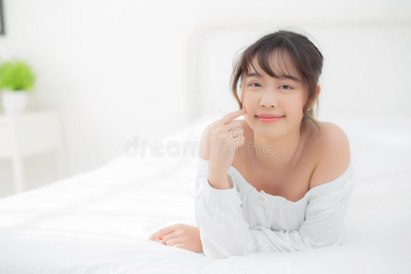 Portrait beautiful young asian woman smile while wake up healthy and wellness at morning in the bedroom. Beauty asia girl lying skin care and makeup cosmetic stock photo