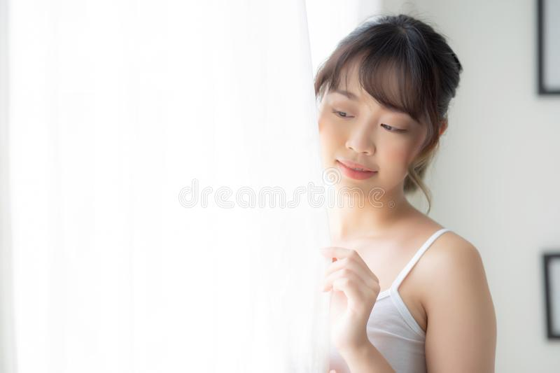 Portrait of beautiful young asian woman standing look at the window and smile while wake up with sunlight at morning. Girl happy with fresh and cheerful royalty free stock photos