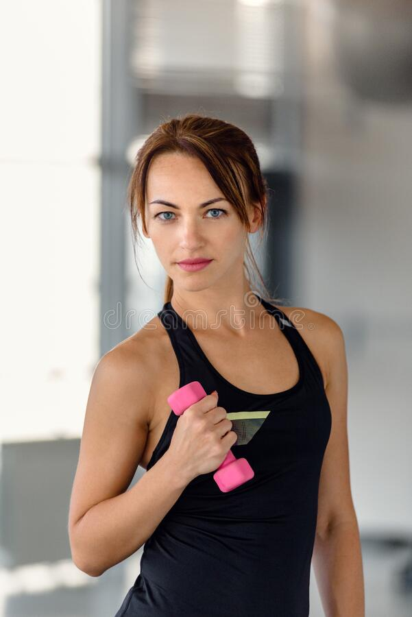 Athletic woman with dumbbell stock photography