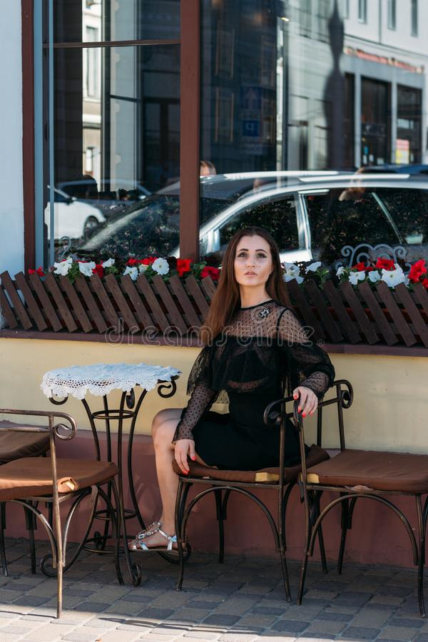 Portrait of a beautiful, young, attractive girl who sits on the street in a cafe. waiting for breakfast, summer, date. dream stock image