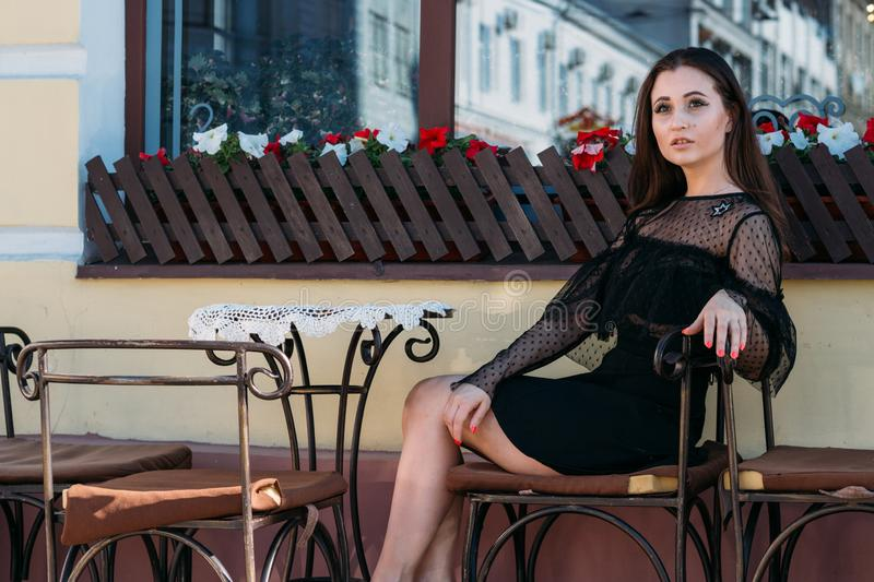 Portrait of a beautiful, young, attractive girl who sits on the street in a cafe. waiting for breakfast, summer, date. dream royalty free stock photos