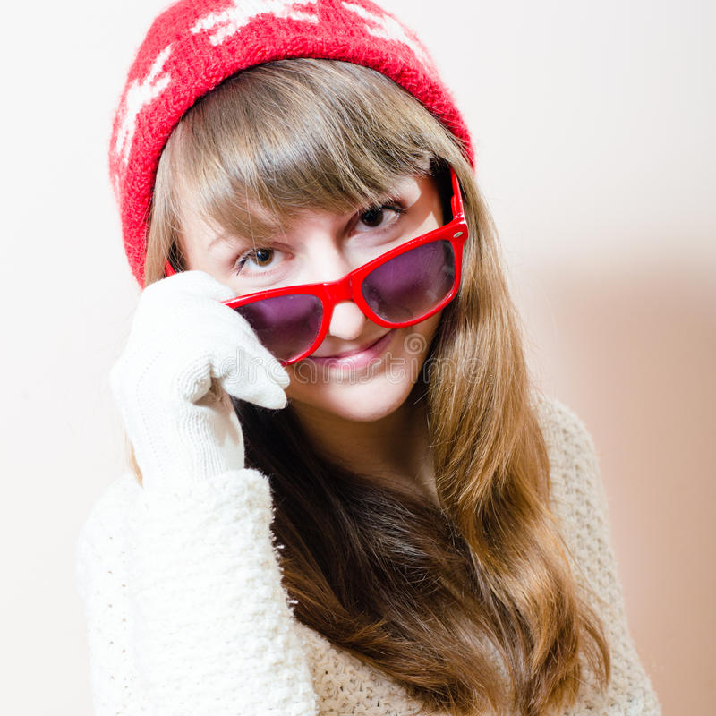 Portrait of beautiful young attractive woman in knitted sweater gloves & hat lowered red glasses looking at camera royalty free stock image