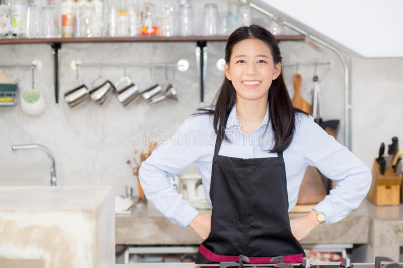 Portrait of beautiful young barista, asian woman is a employee standing in counter coffee shop royalty free stock photography