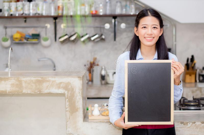 Portrait of beautiful young barista, asian woman is a employee standing holding chalkboard stock photos