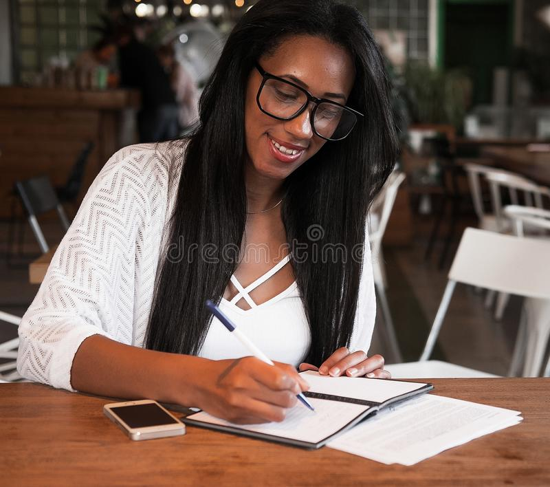Young black woman sitting at cafe and writing notes, lifestyle concept royalty free stock photo