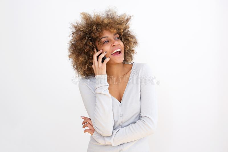Beautiful young black woman talking on cellphone against whit background. Portrait of beautiful young black woman talking on cellphone against whit background stock photos