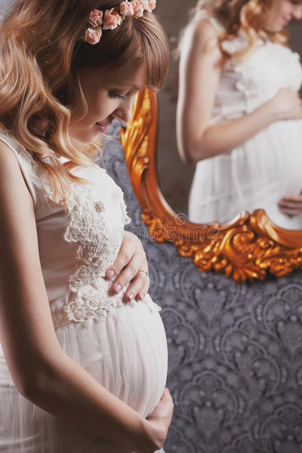 Portrait of a beautiful, young, blond long-haired pregnant mother in a white vintage peignoir, with a floral vink on her head. Looks at the belly and royalty free stock image