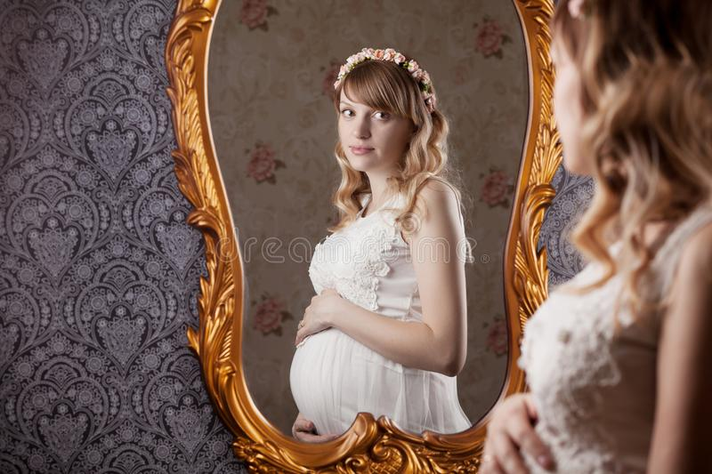Portrait of a beautiful, young, blond long-haired pregnant mother in a white vintage peignoir, with a floral vink on her head. Looks at the belly and stock photo