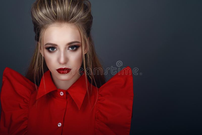 Portrait of beautiful young blond model with perfect provocative make up and stylish creative hairstyle wearing bright red blouse stock photos
