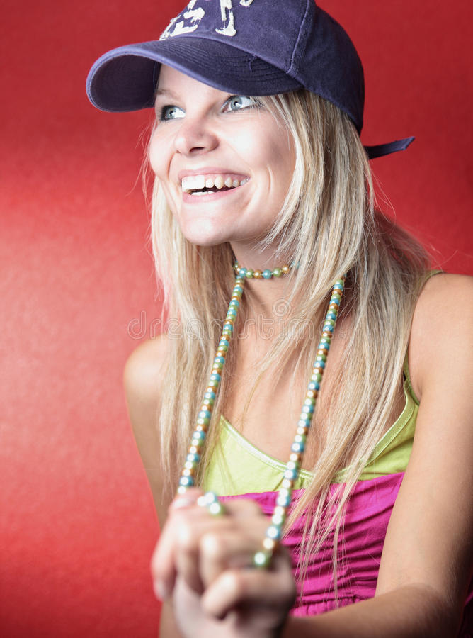 Portrait of a beautiful young blonde. Woman wearing a baseball cap and a necklace posing in front of a red wall stock photo