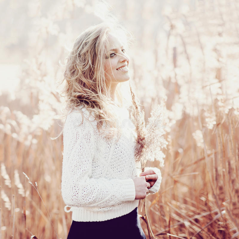 Portrait of a beautiful young blonde girl in a field in white pullover, smiling, concept beauty and health royalty free stock photography