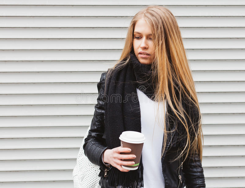 Portrait of a beautiful young blonde girl with long hair posing on a street with coffee and a backpack. Outdoor, warm color. Close royalty free stock images