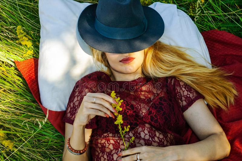 Portrait of a beautiful young blonde girl resting in nature. Girl lying in a field on the grass and smiling. in the hands of the g royalty free stock photography