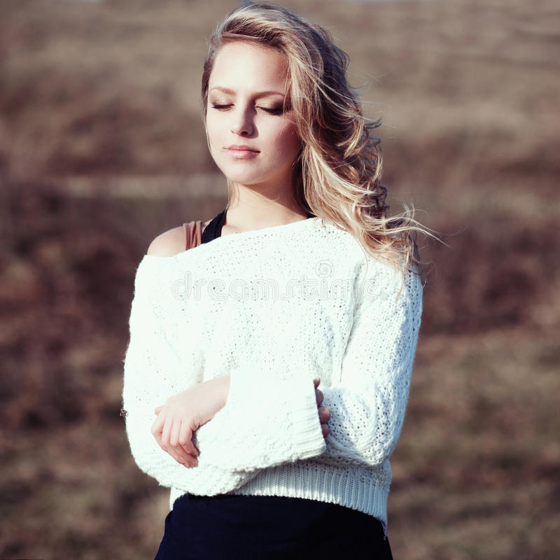 Portrait of a beautiful young blonde girl in the white pullovers stock photo