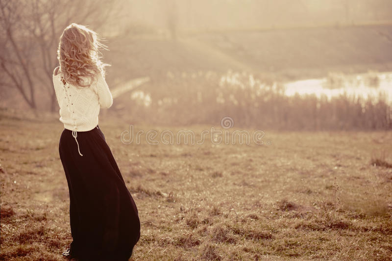 Portrait of a beautiful young blonde girl in the white pullovers, standing with his back stock photo