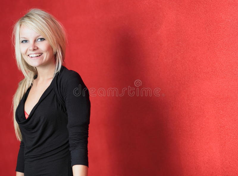 Portrait of a beautiful young blonde woman. Posing in front of a red wall stock image