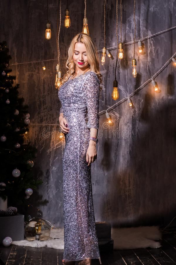 Portrait of Beautiful young blonde woman in evening dress. Holidays, celebration and people concept. Young beautiful women in dress on christmas with red lips stock image