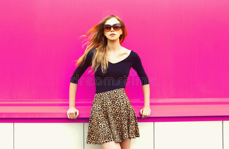 Portrait beautiful young blonde woman with hair blowing in wind posing in leopard skirt and sunglasses royalty free stock photography