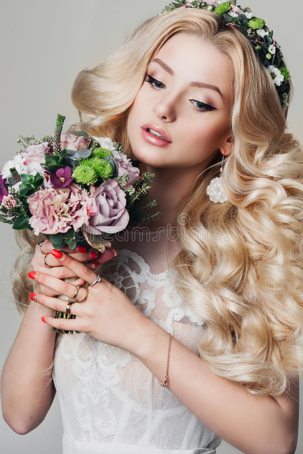 Portrait of a beautiful young blonde woman with long curly hair and eyes royalty free stock image