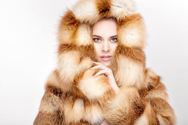 Portrait of beautiful young blonde woman in luxury Fox fur coat. Winter fashion on grey background royalty free stock photography