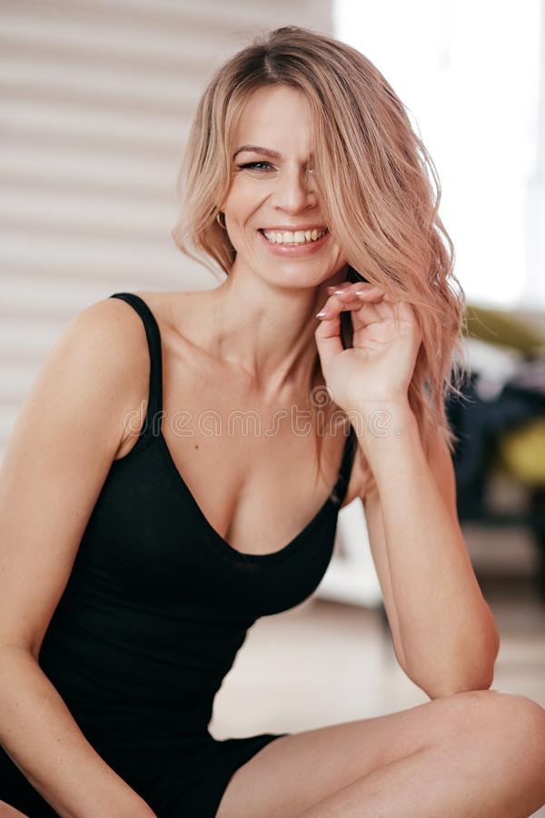 Portrait of beautiful young blonde woman with makeup in black dress royalty free stock photography