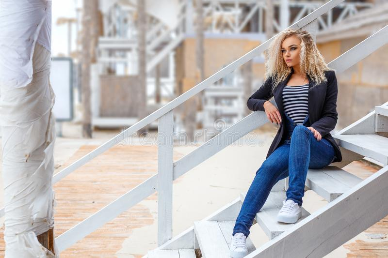 Portrait of a beautiful young blonde woman who poses on camera on the street.  royalty free stock photos