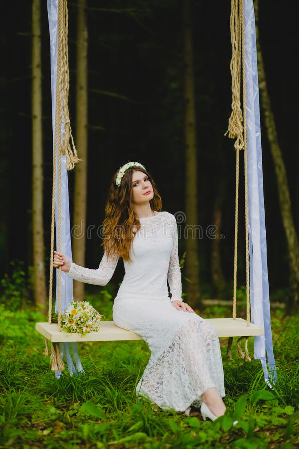 Portrait of beautiful young bride sitting on the rope swing stock image