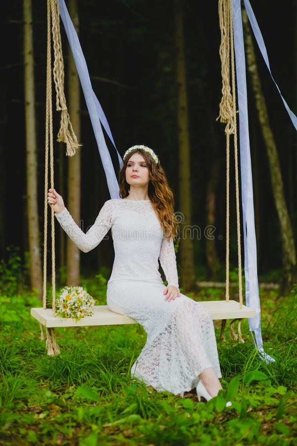 Portrait of beautiful young bride sitting on the rope swing stock photography