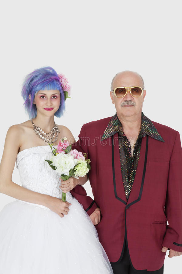 Portrait of beautiful young bride standing arm in arm with father royalty free stock image
