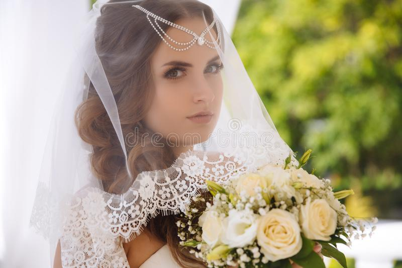 Portrait of a beautiful young bride wearing a white lace veil, worried on her wedding day, holding a wedding bouquet. stock photos