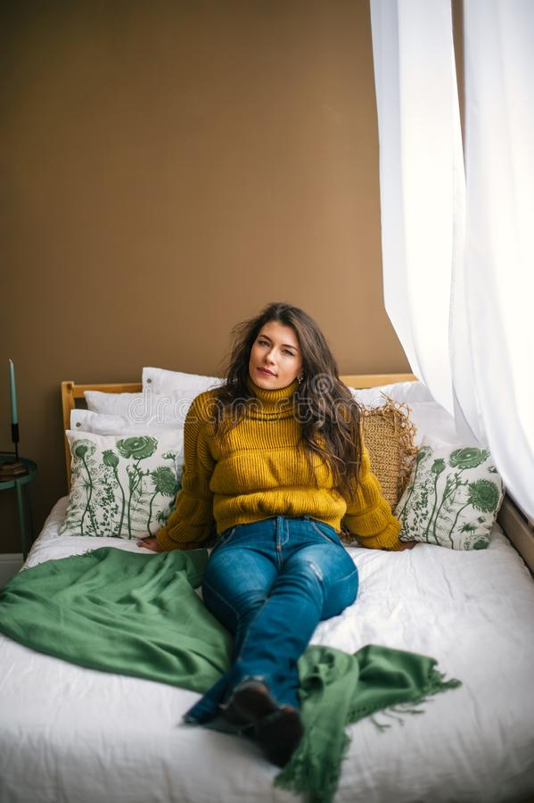 Portrait of beautiful young brunette in jeans and sweater sitting on the bed stock images
