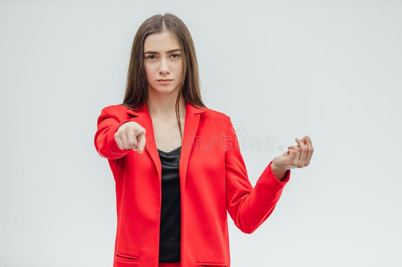 Portrait of a beautiful young brunette. Stretches your hand in congratulations. Dressed in a red jacket. Gray background stock images