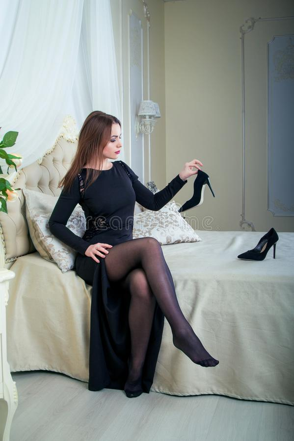 Portrait of beautiful young brunette woman sitting in bedroom, holding shoe royalty free stock photo